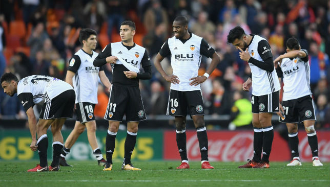 Valencia players look dejected after their loss to Real Madrid.