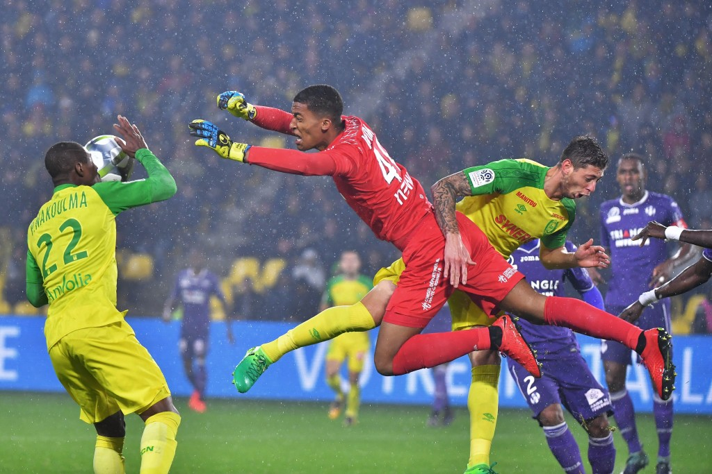 Alban Lafont (in red) tussles with Nantes' forwards Prejuce Nakoulma (L) and Emiliano Sala.
