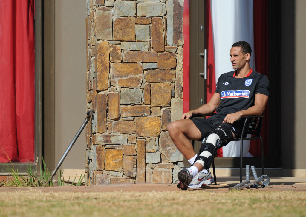 England's injured Rio Ferdinand watches as his teammates take part in a training session at the Royal Bafokeng Sports Campus near Rustenburg on 8 June, 2010, ahead of the 2010 World Cup football tournament in South Africa. AFP PHOTO/PAUL ELLIS (Photo credit should read PAUL ELLIS/AFP/Getty Images)