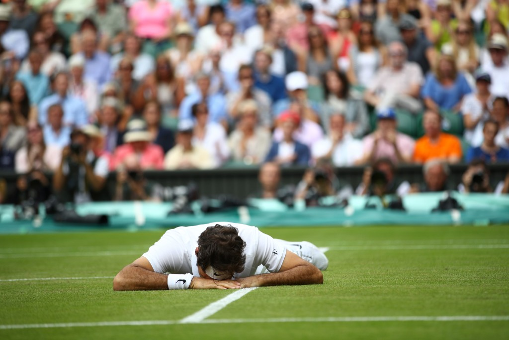 Switzerland's Roger Federer falls to the ground while trying to return to Canada's Milos Raonic during their men's semi-final match on the twelfth day of the 2016 Wimbledon Championships at The All England Lawn Tennis Club in Wimbledon, southwest London, on July 8, 2016. / AFP / POOL AND AFP / Clive BRUNSKILL / RESTRICTED TO EDITORIAL USE (Photo credit should read CLIVE BRUNSKILL/AFP/Getty Images)