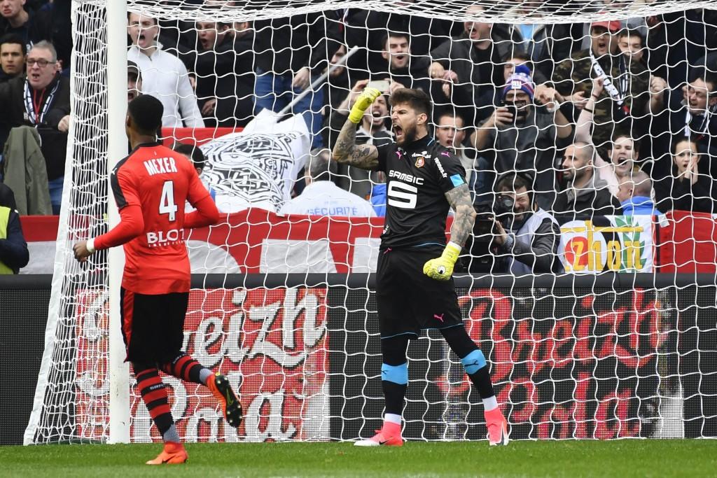 Benoit Costil - then of Rennes - celebrates after saving Alexandre Lacazette's attempt for Lyon.