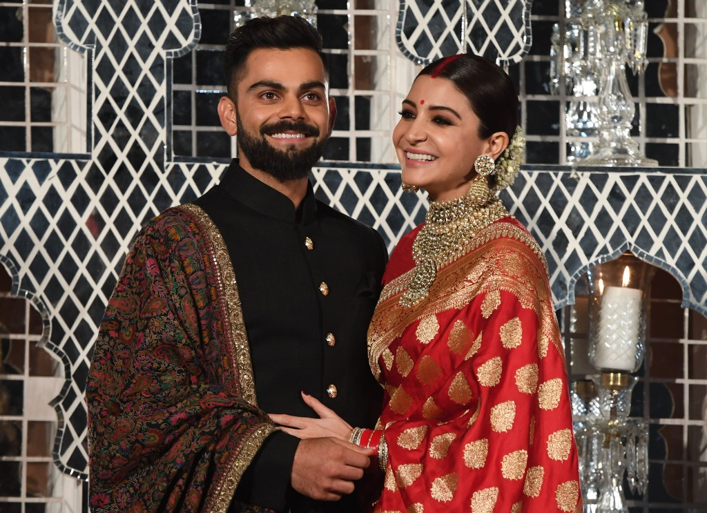 "Indian cricketer Virat Kohli (L) and Bollywood actress Anushka Sharma, who were recently married in Italy, pose during a reception in New Delhi on December 21, 2017. The wedding in Tuscany on December 11 ended weeks of speculation in the gossip pages of India's newspapers and on the airwaves of the country's excitable 24-hour news channels that the couple had recently got engaged. Kohli and Sharma, dubbed ""Virushka"" by local media, have generated the same sort of excitement and coverage in India as Britain's Prince Harry and fiance Meghan Markle have in the West. / AFP PHOTO / PRAKASH SINGH (Photo credit should read PRAKASH SINGH/AFP/Getty Images)"