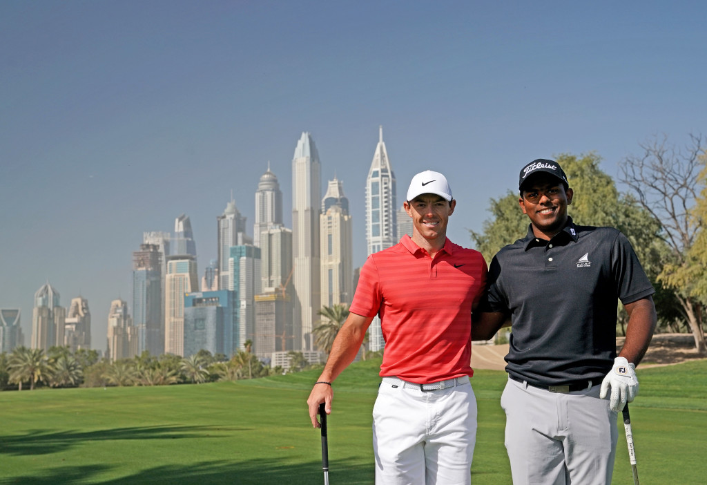 DUBAI, UNITED ARAB EMIRATES - JANUARY 23:  Rayhan Thomas of India poses with Rory McIlroy of Northern Ireland on the 13th hole during a practice round together as a preview for the Omega Dubai Desert Classic on the Majlis Course at The Emirates Golf Club on January 23, 2018 in Dubai, United Arab Emirates.  (Photo by David Cannon/Getty Images)
