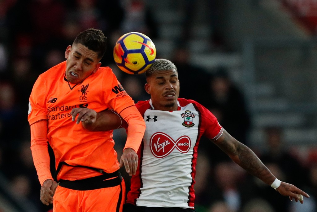 Liverpool's Brazilian midfielder Roberto Firmino (L) jumps against Southampton's Gabonese midfielder Mario Lemina (R) during the English Premier League football match between Southampton and Liverpool at St Mary's Stadium in Southampton, southern England on February 11, 2018. / AFP PHOTO / Adrian DENNIS / RESTRICTED TO EDITORIAL USE. No use with unauthorized audio, video, data, fixture lists, club/league logos or 'live' services. Online in-match use limited to 75 images, no video emulation. No use in betting, games or single club/league/player publications. / (Photo credit should read ADRIAN DENNIS/AFP/Getty Images)