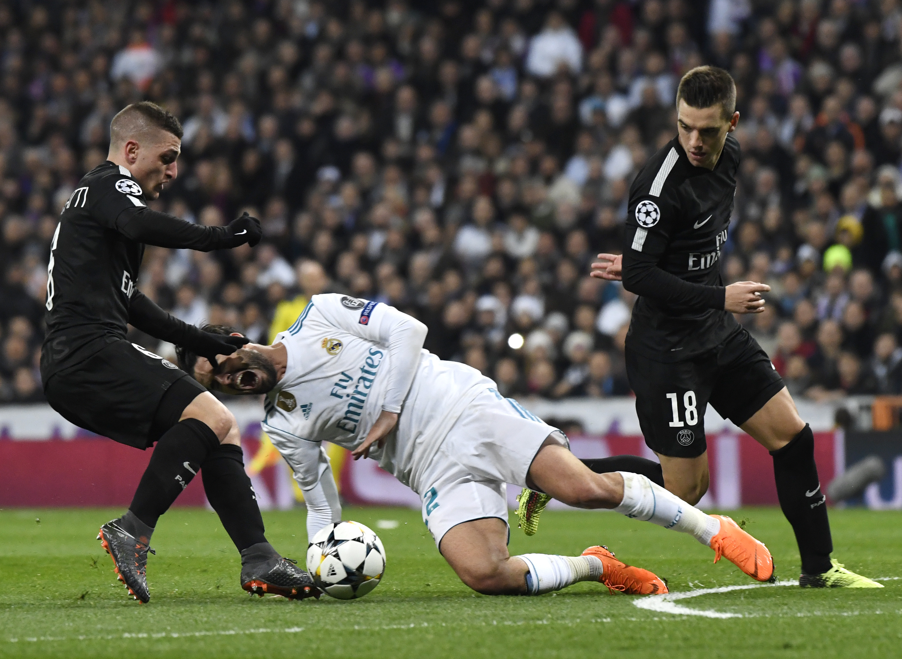Real Madrid's Spanish midfielder Isco (c) vies with Paris Saint-Germain's Marco Verratti (l).