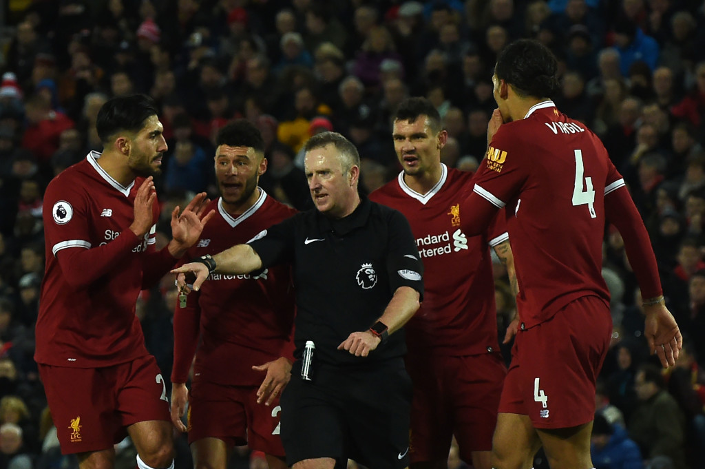 Referee Johnathan Moss (C) awards the first penalty as Liverpool players discuss during the English Premier League football match between Liverpool and Tottenham Hotspur at Anfield in Liverpool, north west England on February 4, 2018. / AFP PHOTO / PAUL ELLIS / RESTRICTED TO EDITORIAL USE. No use with unauthorized audio, video, data, fixture lists, club/league logos or 'live' services. Online in-match use limited to 75 images, no video emulation. No use in betting, games or single club/league/player publications. / (Photo credit should read PAUL ELLIS/AFP/Getty Images)