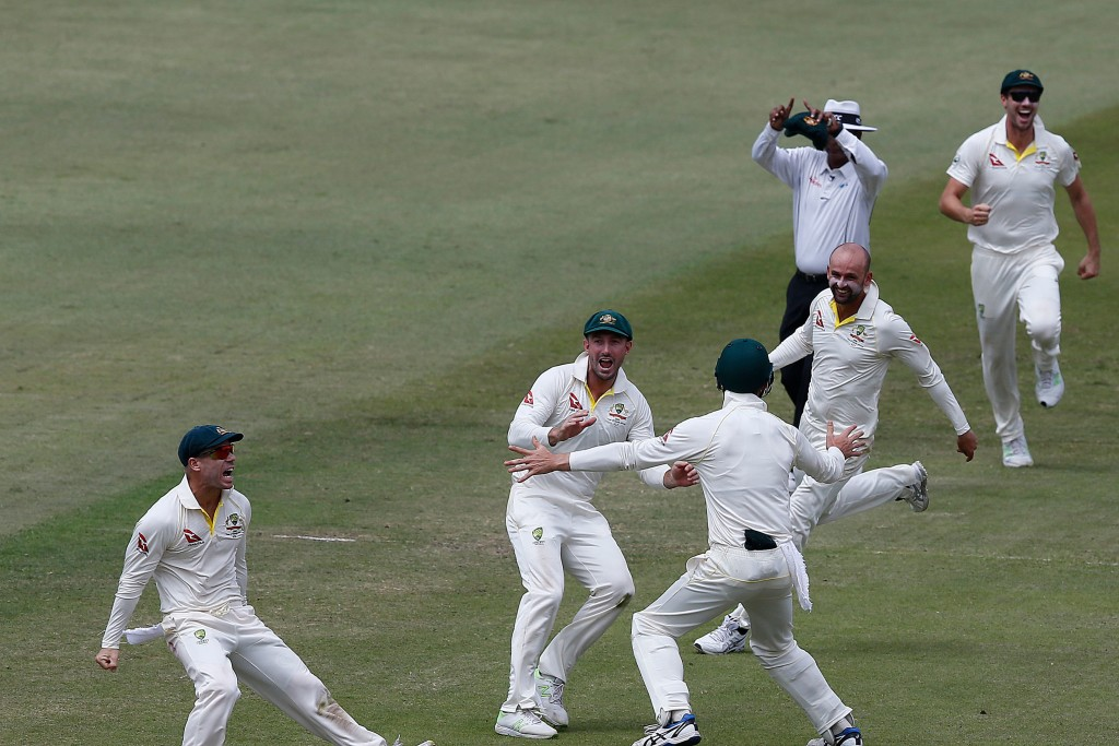 Australian bowler Nathan Lyon (3R) celebrates with teammates after taking a throw from David Warner (L) to run out unseen South African batsman AB de Villiers during the fourth day of the first Test cricket match between South Africa and Australia at The Kingsmead Stadium in Durban on March 4, 2018. / AFP PHOTO / MARCO LONGARI (Photo credit should read MARCO LONGARI/AFP/Getty Images)