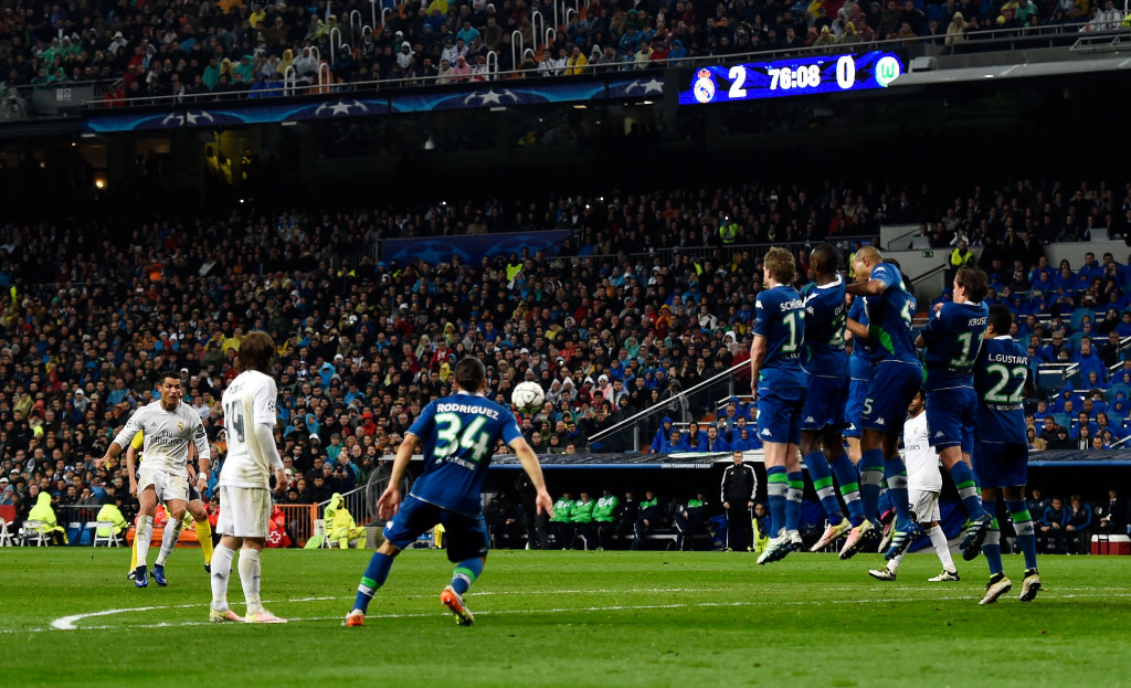 MADRID, SPAIN - APRIL 12: Cristiano Ronaldo of Real Madrid (L) scores their their goal from a free kick and completes his hat trick during the UEFA Champions League quarter final second leg match between Real Madrid CF and VfL Wolfsburg at Estadio Santiago Bernabeu on April 12, 2016 in Madrid, Spain. (Photo by Mike Hewitt/Getty Images)