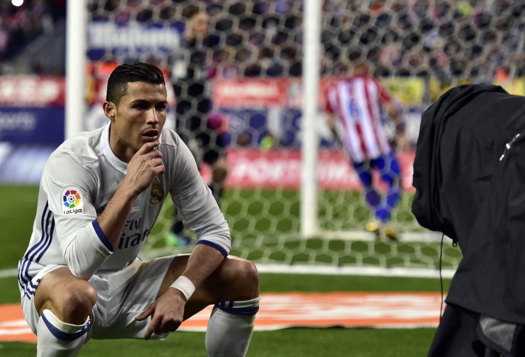 TOPSHOT - Real Madrid's Portuguese forward Cristiano Ronaldo poses in front of a TV camera as he celebrates after scoring during the Spanish league football match Club Atletico de Madrid vs Real Madrid CF at the Vicente Calderon stadium in Madrid, on November 19, 2016. Real Madrid won 3-0. / AFP / GERARD JULIEN (Photo credit should read GERARD JULIEN/AFP/Getty Images)