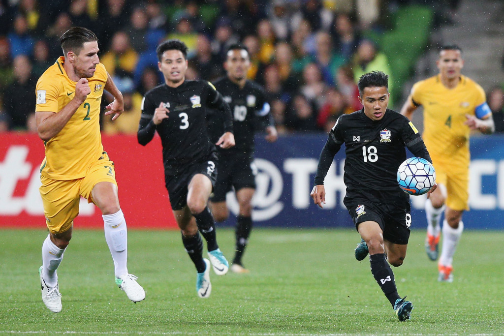 Chanathip Songkrasin of Thailand (r) tries to evade Australia's defenders.
