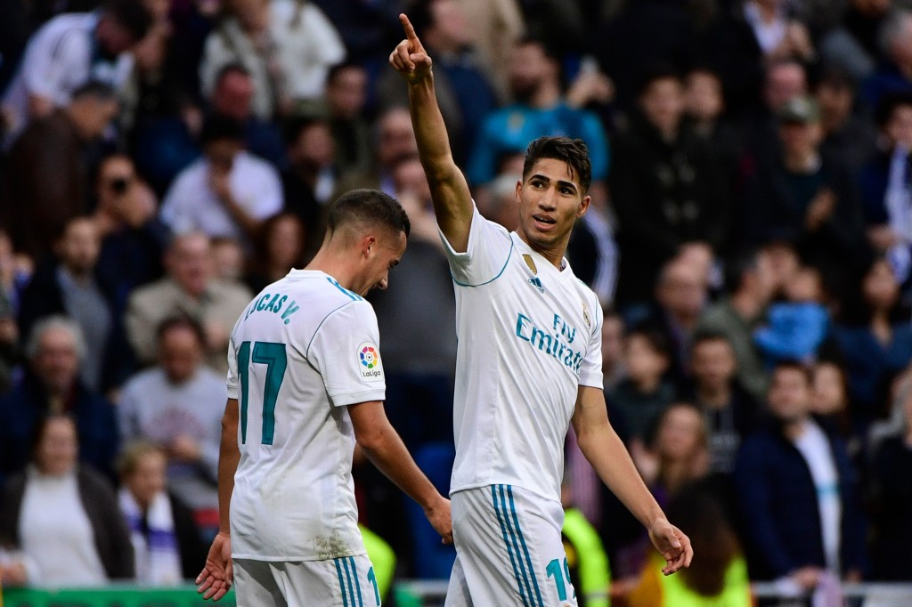 Real Madrid's Spanish-Moroccan defender Achraf Hakimi (R) celebrates with Real Madrid's Spanish midfielder Lucas Vazquez after scoring his team's fifth goal during the Spanish league football match between Real Madrid and Sevilla at the Santiago Bernabeu Stadium in Madrid on December 9, 2017. / AFP PHOTO / PIERRE-PHILIPPE MARCOU (Photo credit should read PIERRE-PHILIPPE MARCOU/AFP/Getty Images)