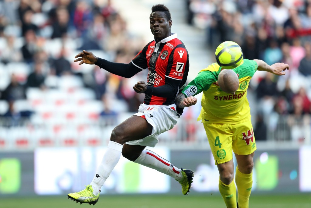 """Nice's Italian forward Mario Balotelli (L) fights for the ball with Nantes' French defender Nicolas Pallois (R) during the French L1 football match Nice vs Nantes on February 18, 2018 at the """"Allianz Riviera"""" stadium in Nice, southeastern France. / AFP PHOTO / VALERY HACHE (Photo credit should read VALERY HACHE/AFP/Getty Images)"""