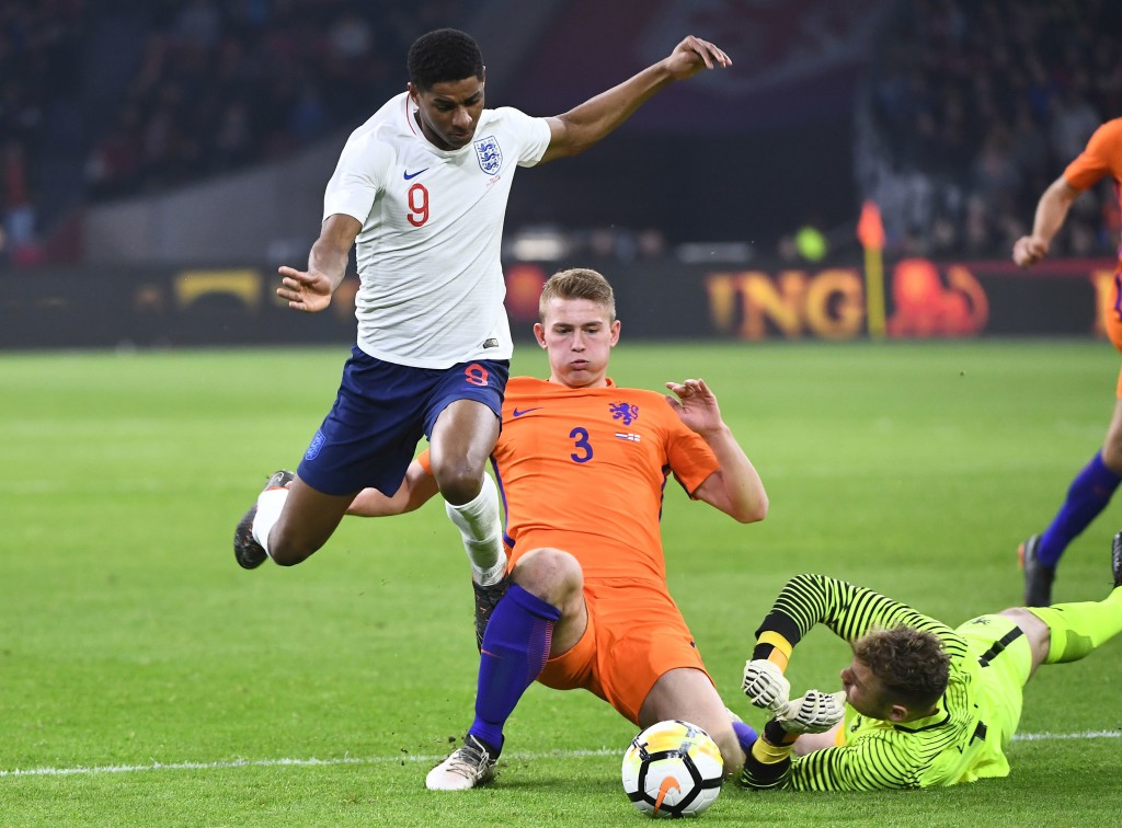 English player Marcus Rashford (l) is stopped by Netherlands defender Matthijs de Ligt and goalkeeper Jeroen Zoet.