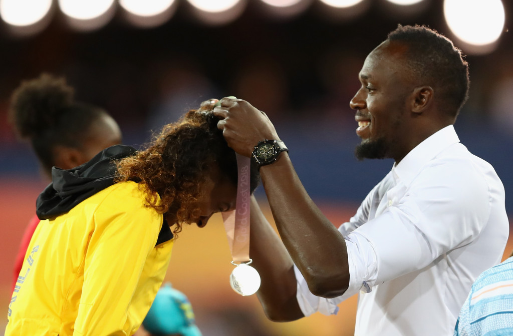 Bolt presenting Jackson with her medal.