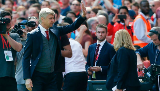 Arsene Wenger waves to the fans.