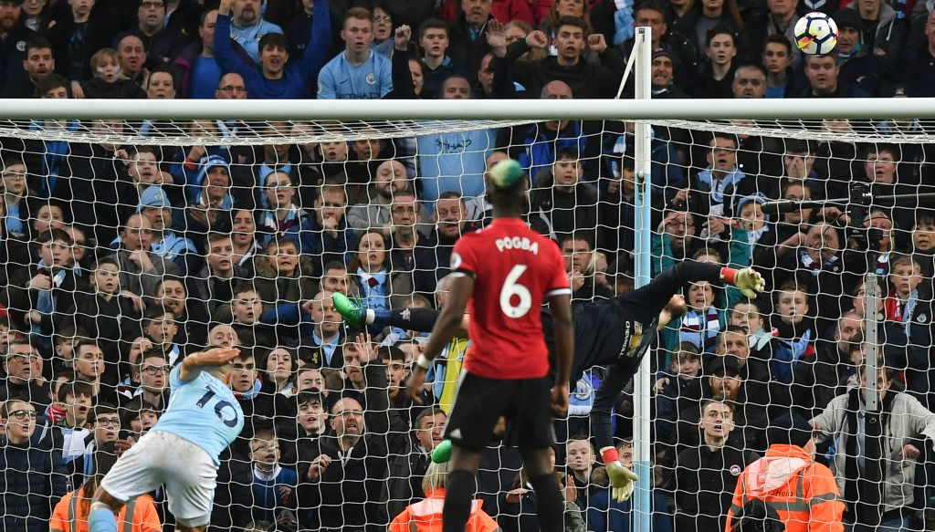 David De Gea somehow tips over Sergio Aguero's header.