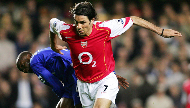 Arsenal's Robert Pires (R) fights off a