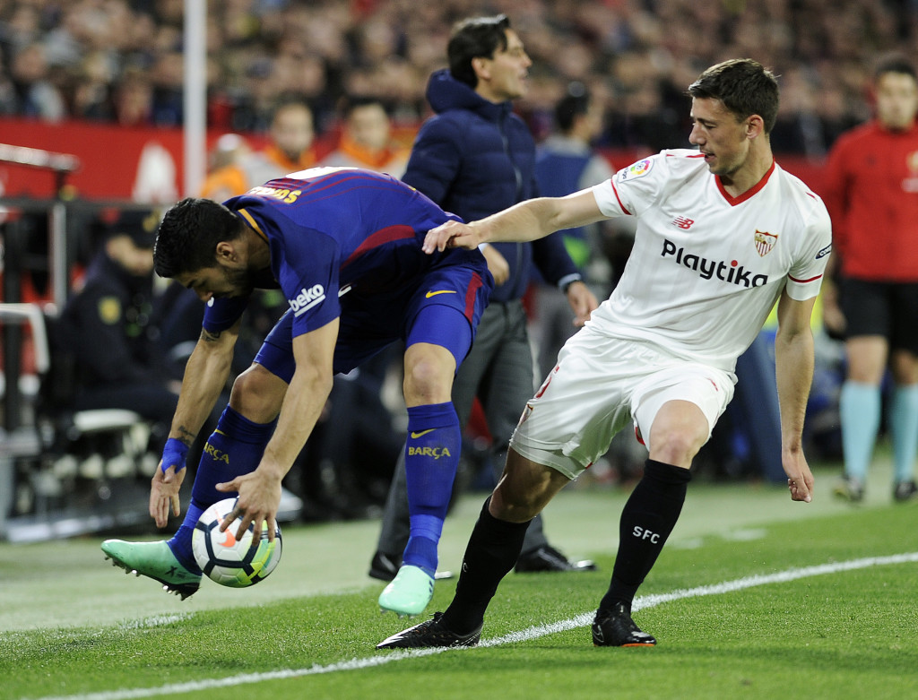 Barcelona's Uruguayan forward Luis Suarez (L) fights for the ball with Sevilla's French defender Clement Lenglet during the Spanish League football match between Sevilla FC and FC Barcelona at the Ramon Sanchez Pizjuan stadium on March 31, 2018. / AFP PHOTO / Cristina Quicler (Photo credit should read CRISTINA QUICLER/AFP/Getty Images)