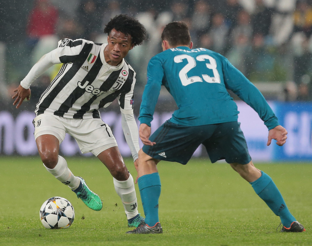 TURIN ITALY- APRIL 03 Juan Cuadrado of Juventus FC is challenged by Mateo Kovacic of Real Madrid during the UEFA Champions League Quarter Final Leg One match between Juventus and Real Madrid at Allianz Stadium