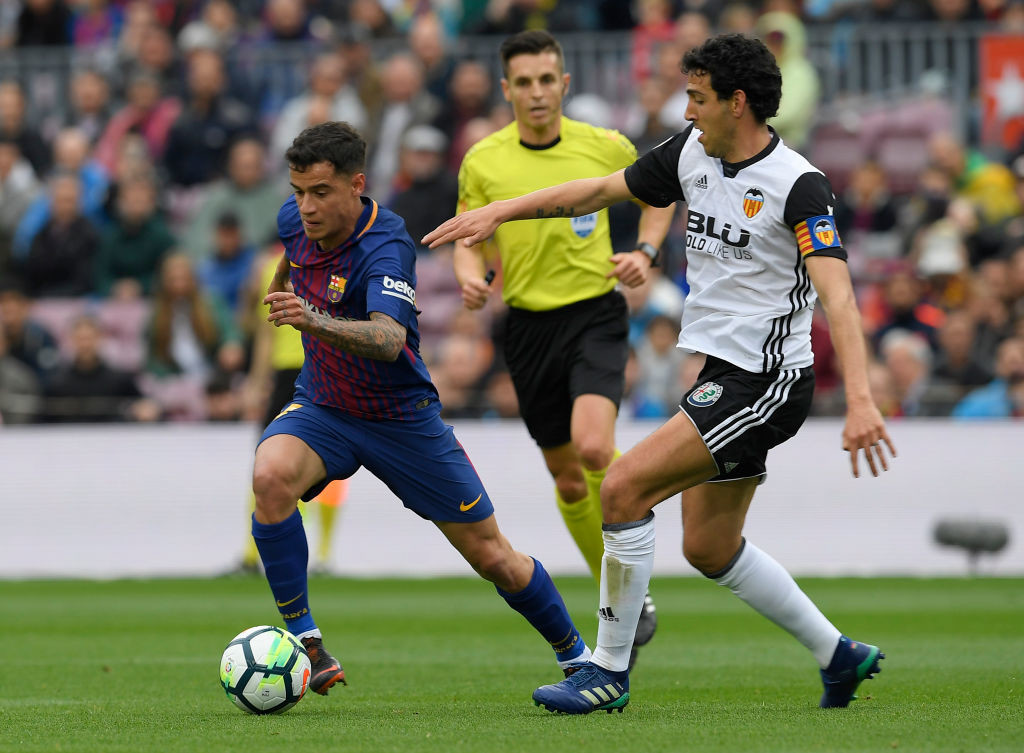 Philippe Coutinho (L) drives forward.