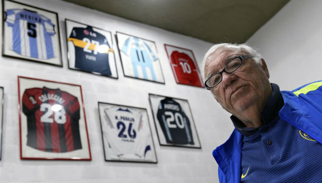 Maddoni poses next to jerseys given to him by football stars he scouted.
