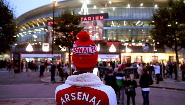 An Arsenal fan waits outside the Emirates Stadium