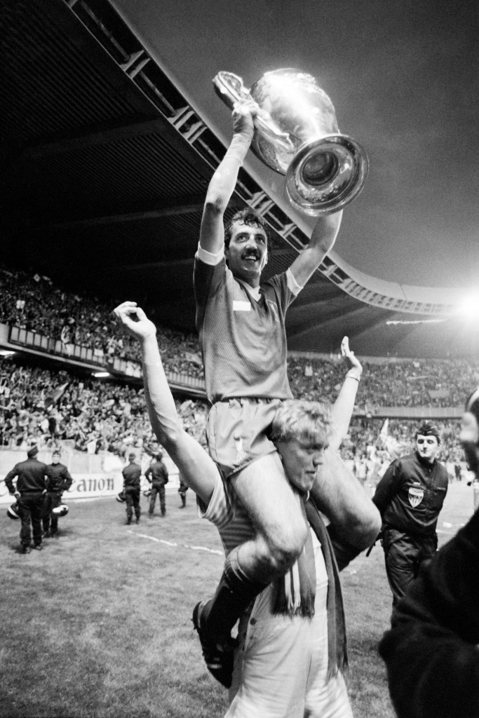 Alan Kennedy sits on a teammates's shoulders as he raises the trophy.