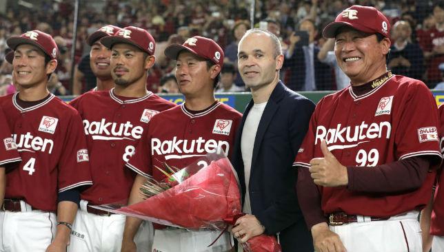 Andres Iniesta (2R) poses with Japan's Tohoku Rakuten Golden Eagles baseball players and manager Masataka Nashida (R)