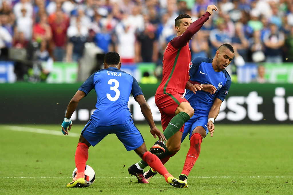 TOPSHOT - France's forward Dimitri Payet (R) crashes into Portugal's forward Cristiano Ronaldo as France's defender Patrice Evra snatches the ball during the Euro 2016 final football match between France and Portugal at the Stade de France in Saint-Denis, north of Paris, on July 10, 2016. / AFP / FRANCK FIFE (Photo credit should read FRANCK FIFE/AFP/Getty Images)