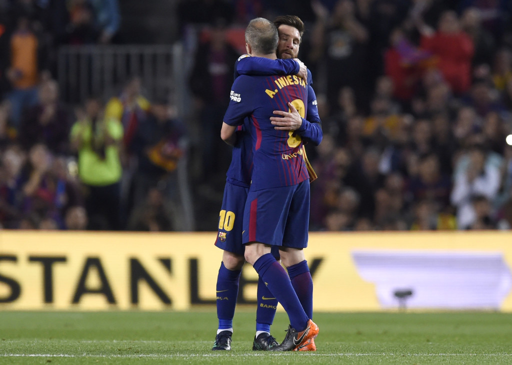 Andres Iniesta of Barcelona is embraced by Lionel Messi.