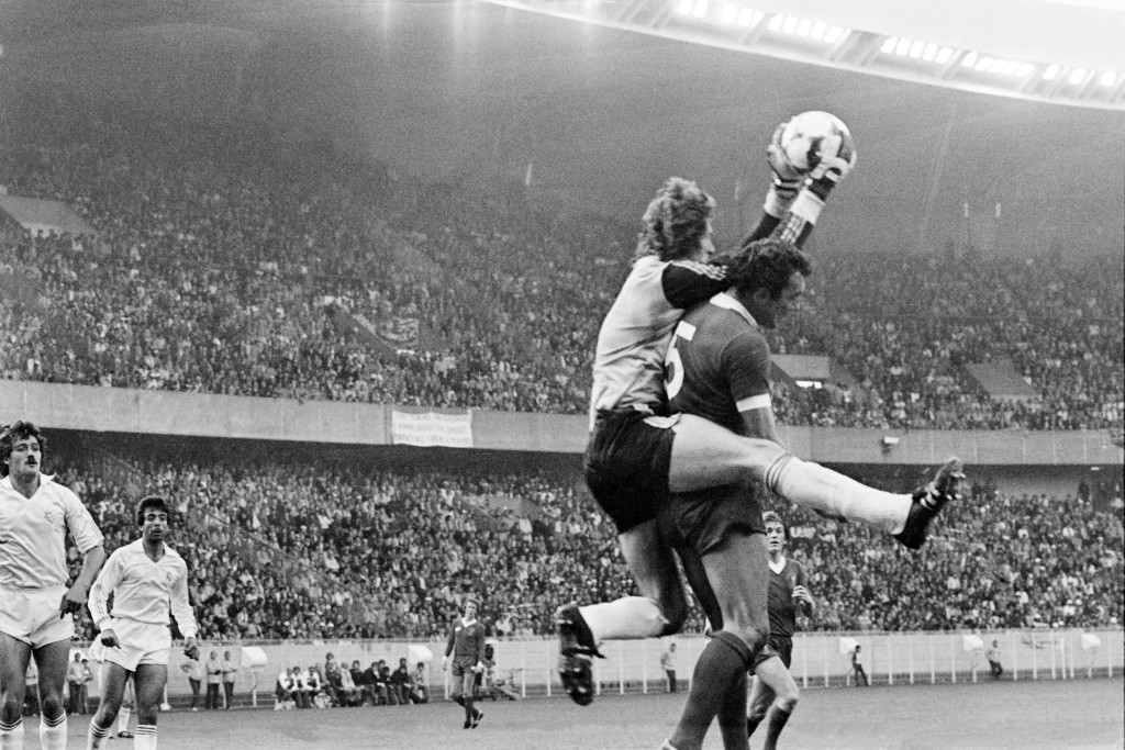 Real Madrid's Spanish goalkeeper Agustin catches the ball over Ray Kennedy.