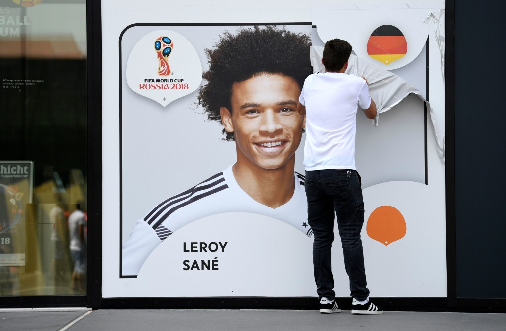 An employee removes a poster bearing a portrait of Leroy Sane from the facade of the Football Museum of the German Football Federation (DFB).