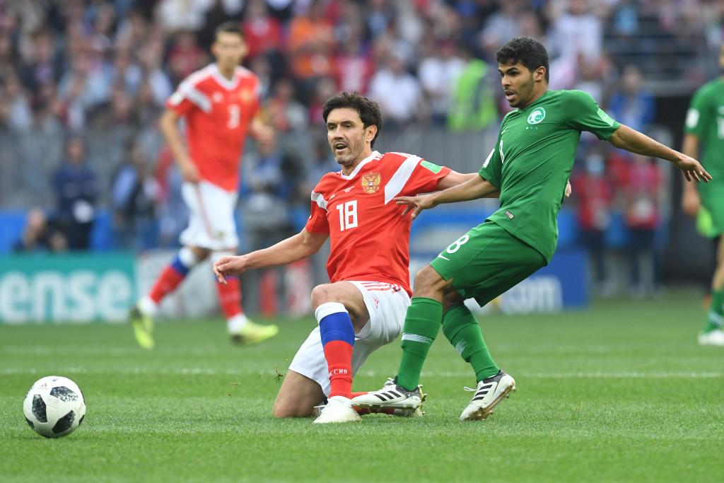 Russia's midfielder Yury Zhirkov (l) vies with Saudi Arabia's midfielder Yahya Al Shehri (r).