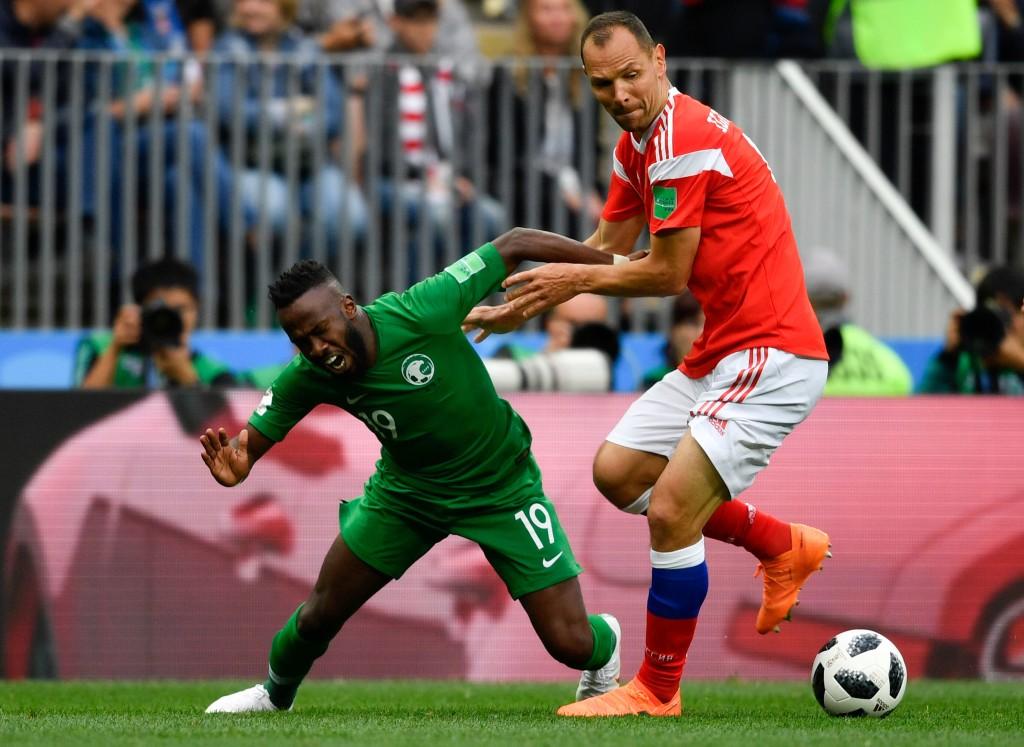 Saudi Arabia's forward Fahad Al-Muwallad (l) and Russia's defender Sergey Ignashevich clash.