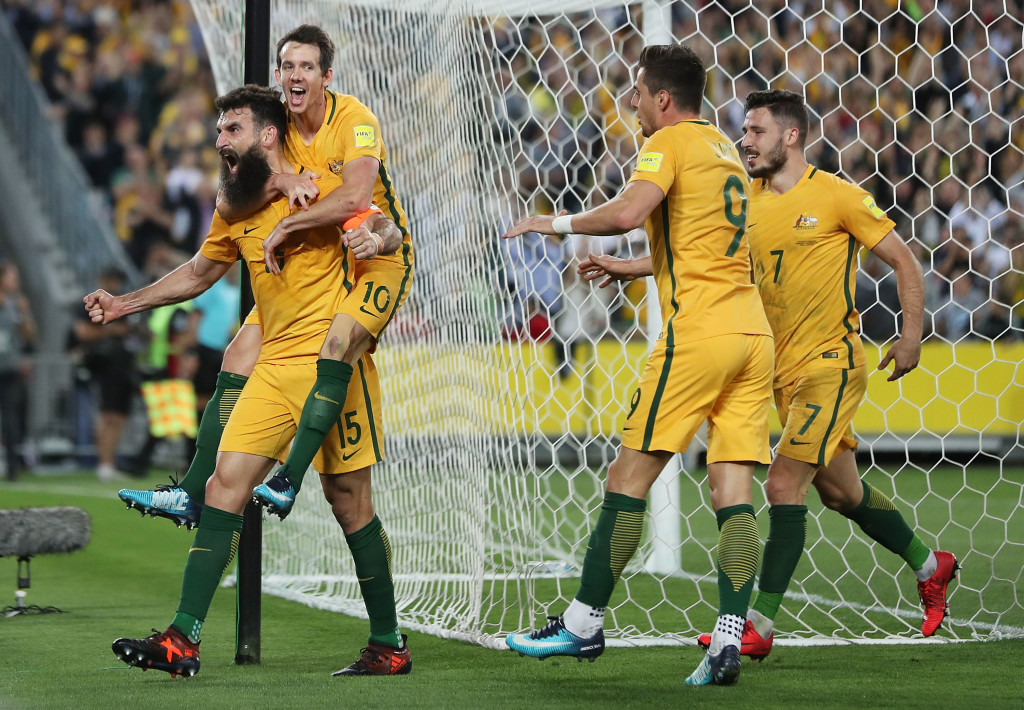 Mile Jedinak celebrates with team mates after scoring one of his hat-trick against Honduras.