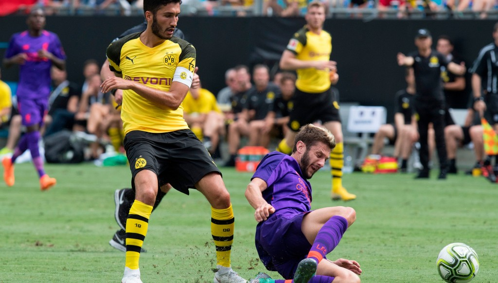 Adam Lallana is tackled by Nuri Sahin