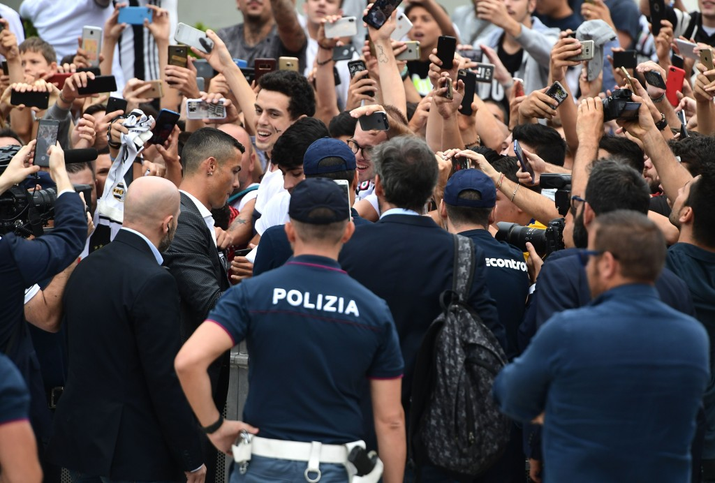 Portuguese footballer Cristiano Ronaldo signs autographs as he arrives on July 16, at the Juventus medical center at the Alliance stadium in Turin. - Cristiano Ronaldo arrived in Turin ahead of his official unveiling as Juventus' superstar summer signing on July 17. (Photo by Miguel MEDINA / AFP) (Photo credit should read MIGUEL MEDINA/AFP/Getty Images)