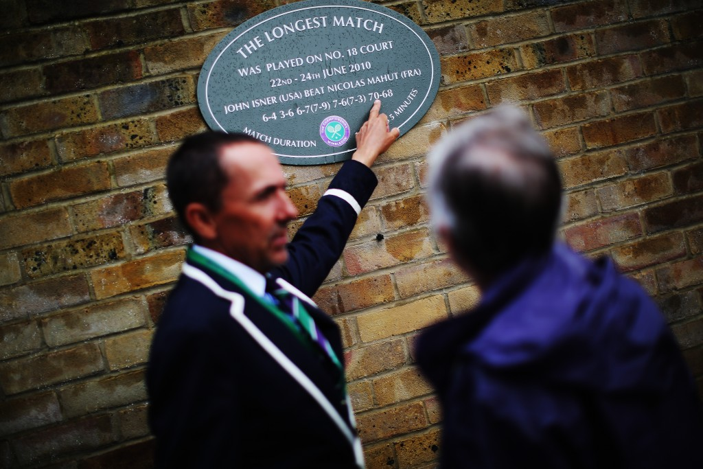 LONDON, ENGLAND - JUNE 28: A Wimbledon official points out the plague that is on the outside of Court 18 to commemorate the longest match which was between John Isner and Nicolas Mahut in 2010 on day six of the Wimbledon Lawn Tennis Championships at the All England Lawn Tennis and Croquet Club at Wimbledon on June 28, 2014 in London, England. (Photo by Dan Kitwood/Getty Images)