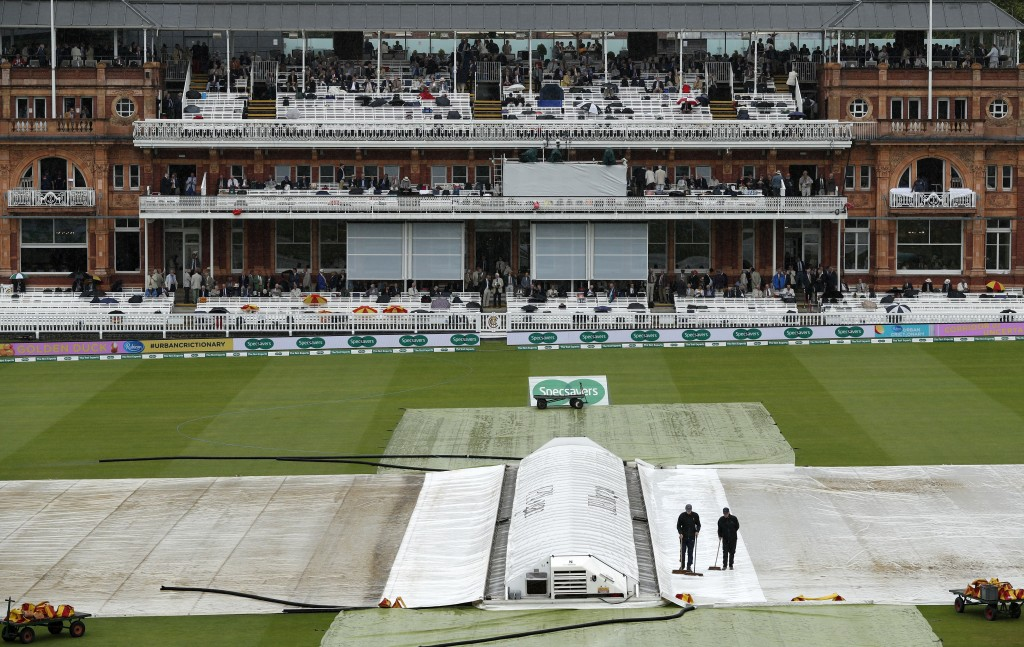 Ground staff sweep rainwater off the covers as rain delays start of play on the first day of the second Test cricket match between England and India at Lord's Cricket Ground in London on August 9, 2018. (Photo by ADRIAN DENNIS / AFP) / RESTRICTED TO EDITORIAL USE. NO ASSOCIATION WITH DIRECT COMPETITOR OF SPONSOR, PARTNER, OR SUPPLIER OF THE ECB (Photo credit should read ADRIAN DENNIS/AFP/Getty Images)