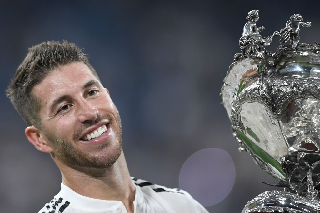 Real Madrid's Spanish defender Sergio Ramos celebrates with the trophy after the Santiago Bernabeu Trophy football match between Real Madrid and AC Milan in Madrid on August 11, 2018. (Photo by GABRIEL BOUYS / AFP) (Photo credit should read GABRIEL BOUYS/AFP/Getty Images)