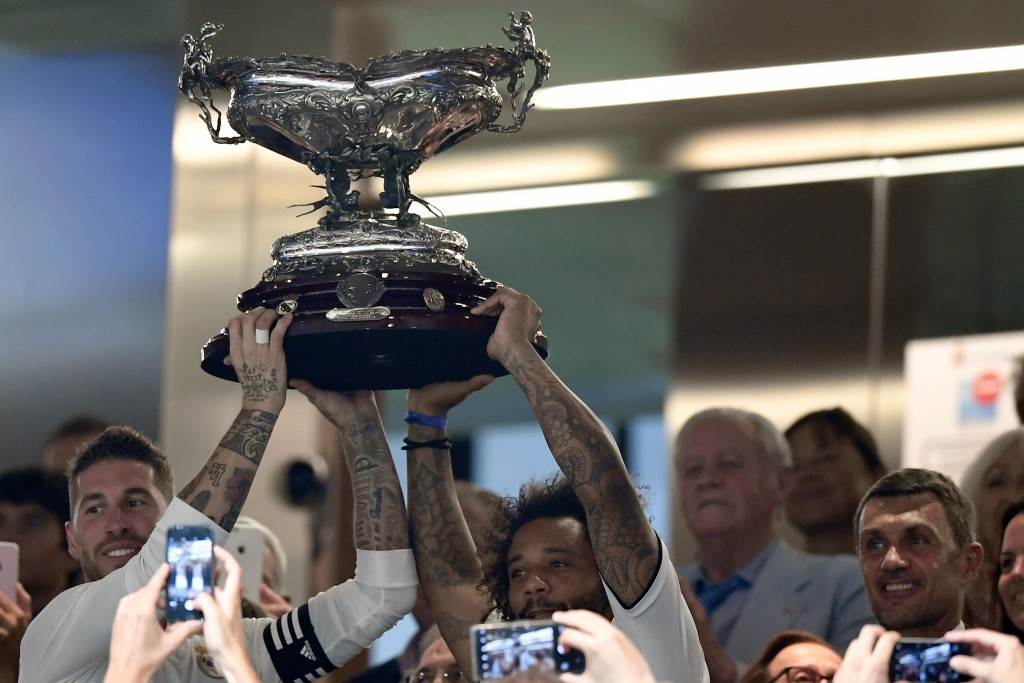 AC Milan legend and newly appointed director Paolo Maldini (R) smiles as Real Madrid's Spanish defender Sergio Ramos (L) and Brazilian defender Marcelo lift the Santiago Bernabeu Trophy after a football match between Real Madrid and AC Milan in Madrid on August 11, 2018. (Photo by GABRIEL BOUYS / AFP) (Photo credit should read GABRIEL BOUYS/AFP/Getty Images)