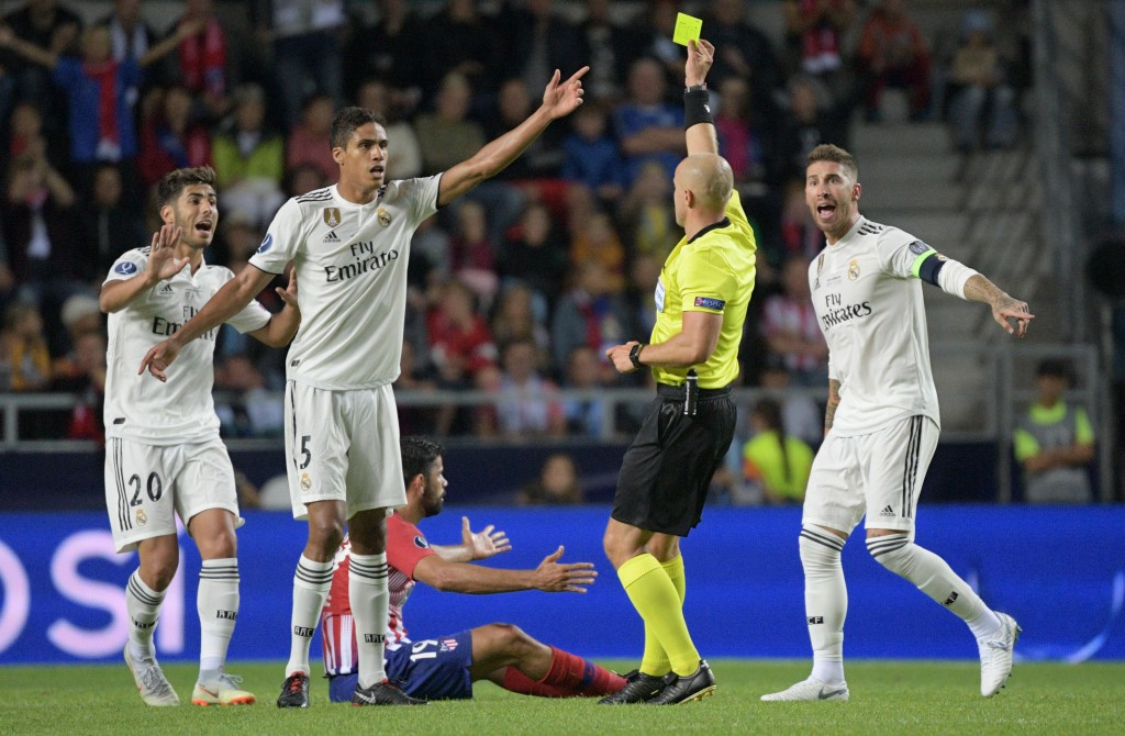 Polish referee Szymon Marciniak (2nd R) shows a yellow card to Real Madrid's Spanish midfielder Marco Asensio (L) as Atletico Madrid's Spanish forward Diego Costa (C) sits on the pitch and Real Madrid's Spanish defender Sergio Ramos (R) and Real Madrid's French defender Raphael Varane (2nd L) gesture during the UEFA Super Cup football match Atletico de Madrid vs Real Madrid CF at the Lillekula Stadium in Tallinn, Estonia, on August 15, 2018. (Photo by Raigo PAJULA / AFP) (Photo credit should read RAIGO PAJULA/AFP/Getty Images)
