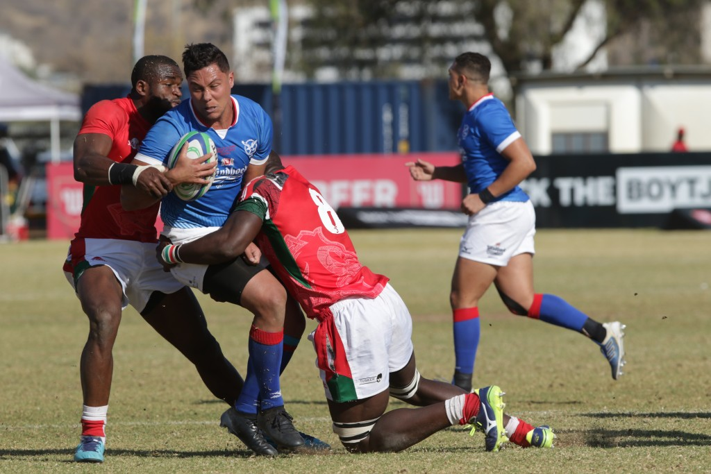 Namibia centre Darryl de la Harpe is tackled by Kenya eighthman Davis Chenge
