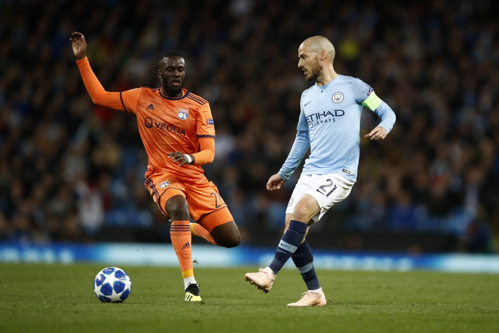 David Silva of Manchester City passes the ball under pressure from Tanguy NDombele.