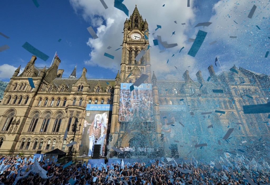 Manchester City's footballers (Below C) celebrate outside Manchester Town Hall as they prepare to take part in a victory parade on an open-topped bus through the streets of Manchester, northwest England, on May 12, 2014, after becoming the English Premier League champions. Manchester City beat West Ham 2-0 on Sunday to finish two points clear of second-placed Liverpool. AFP PHOTO / PAUL ELLIS (Photo credit should read PAUL ELLIS/AFP/Getty Images)