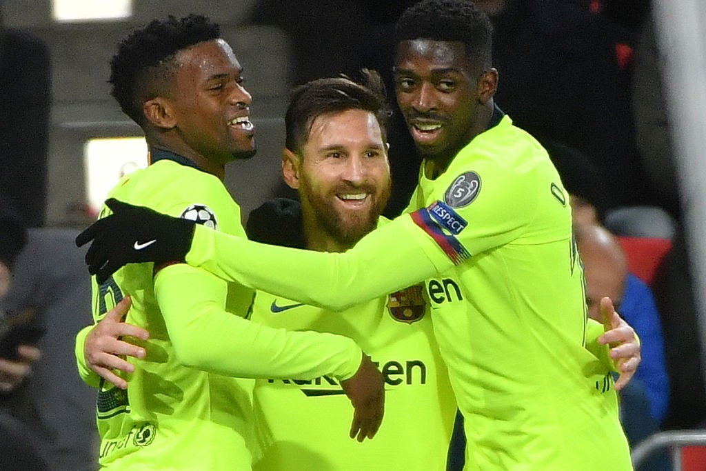 Lionel Messi (C) celebrates with Ousmane Dembele (R) and Nelson Semedo (L)