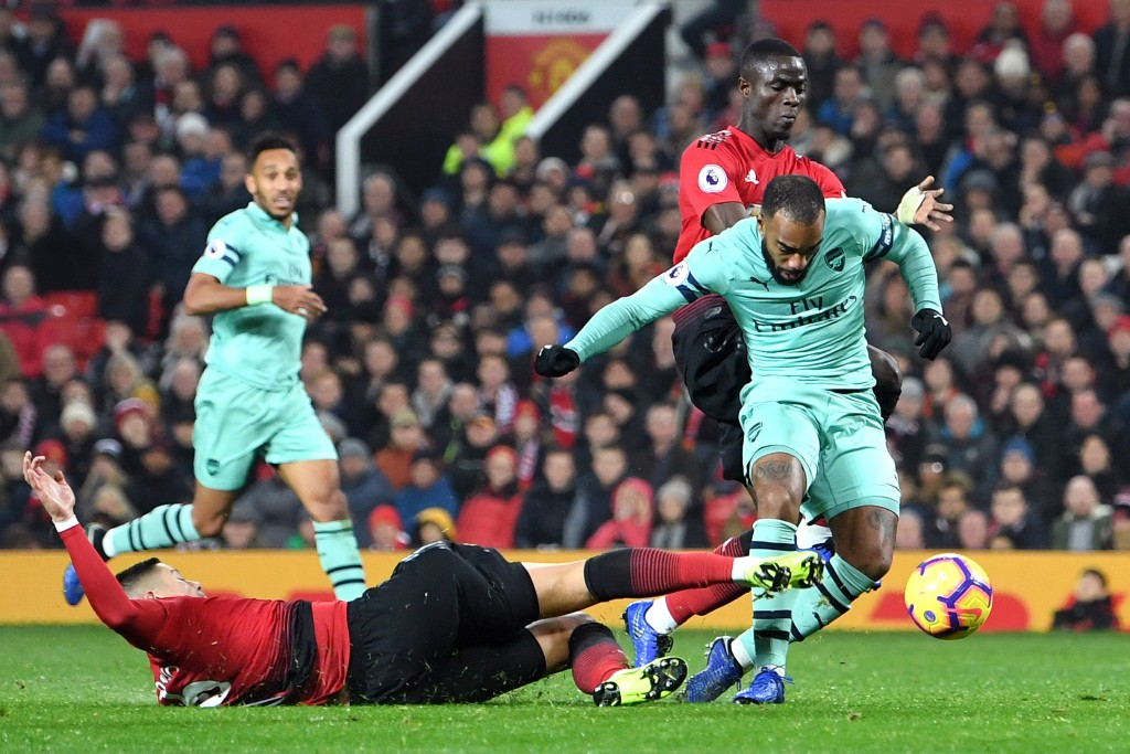 Alexandre Lacazette of Arsenal scores his team's second goal as he is challenged by Marcos Rojo of Manchester United during the Premier League match between Manchester United and Arsenal FC