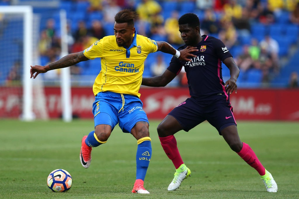 Kevin-Prince Boateng of Las Palmas holds off Barcelona's Samuel Umtiti