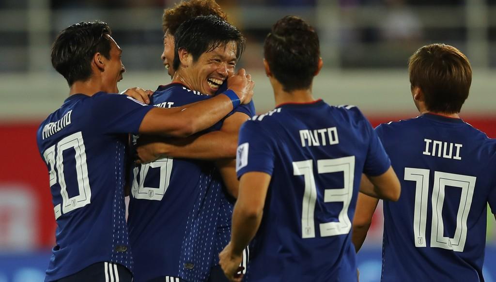 Tsukasa Shiotani (2nd l, facing camera) celebrates with team-mates after putting Japan 2-1 up.