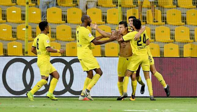 Shirtless Fabio De Lima is mobbed after his 94th minute winner for Wasl.